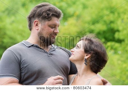 Beloved man and woman hugging each other in park