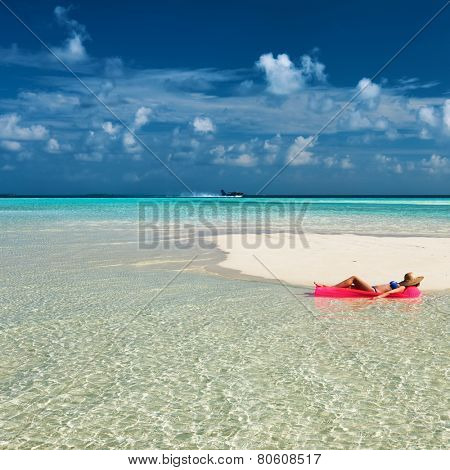 Woman relaxing on inflatable mattress at the beach