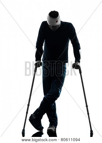 one man injured man standing with crutches in silhouette studio on white background