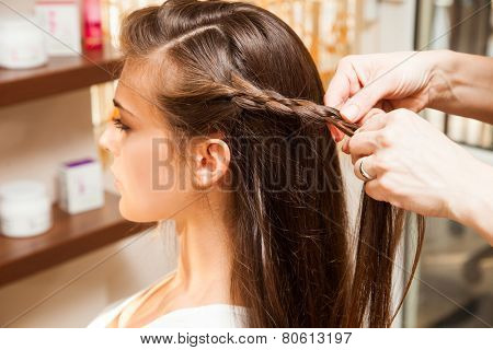 young woman in hair salon making braid of hair