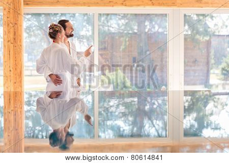 Couple on pool looking relaxed throw window of wellness spa wearing bath robe
