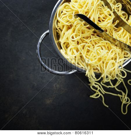 spaghetti in colander on dark vintage background