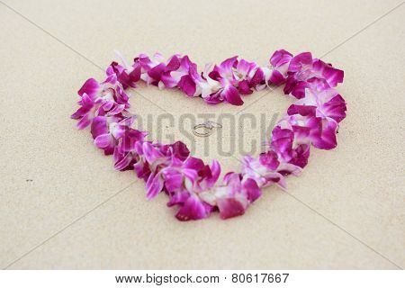 Wedding rings beach love concept. Closeup of two bands in flower heart for casual marriage celebration.