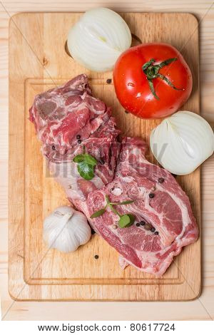 Raw Lamb Leg Chops On A Wooden Chopping Board