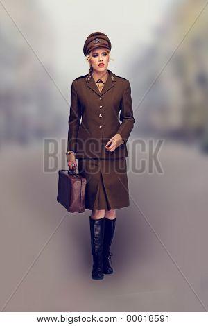 Elegant woman in a brown army uniform walking towards the camera down a blurred misty road in a fashion portrait