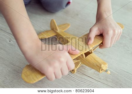Wooden toy airplane in hands held by child