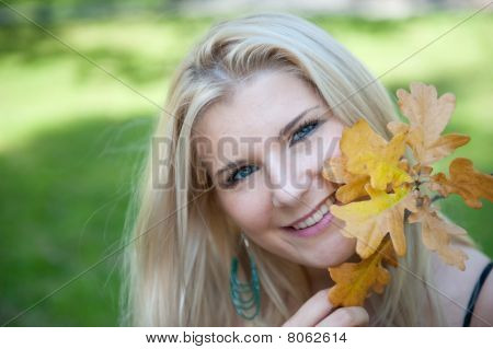 young beautiful autumn woman in yellow park with lots of trees and leafs