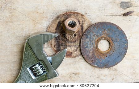 Wrench And Bolt On Wood Background