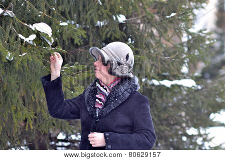 The Woman In A Hat And A Sheepskin Coat Costs Near A Fir-tree In Park.
