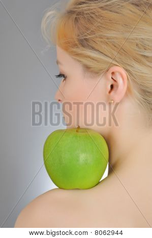 Young Woman Holding Green Apple On  Her Shoulder. Gray Background