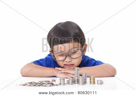Cute boy looking at a stack of coins and stacking them.
