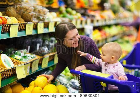 Mother and baby daughter in supermarket buying fruits and vegetables