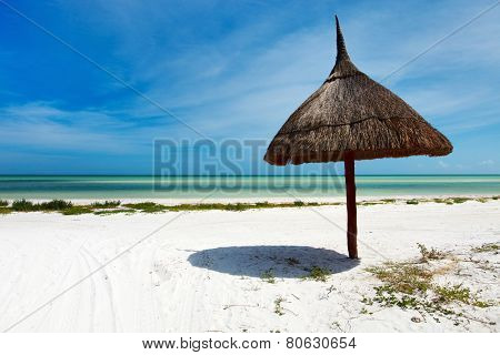 Tropical thatched umbrella on stunning tropical beach at Holbox Mexico