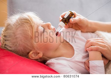 Sick child taking medicine drops