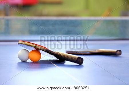 Rackets for tennis and a balls on a blue table with net