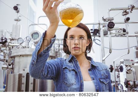 Stylish girl in denim jacket holding beaker of beer in the factory