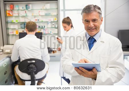 Senior pharmacist using tablet pc at the hospital pharmacy