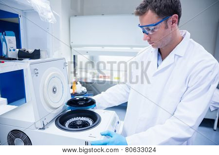 Chemist wearing safety glasses and using a centrifuge in lab
