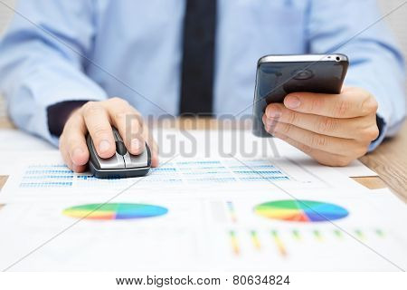 Businessman Is Working On Computer And Using Mouse And Using Smart Mobile Phone At The Same Time On