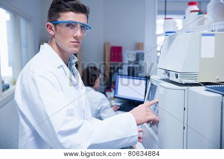 Unsmiling young chemist using the machine in the laboratory