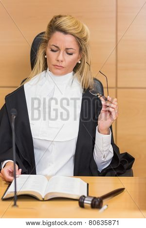 Stern judge reading her notes in the court room