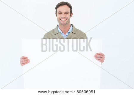 Portrait of happy delivery man holding blank billboard against white background