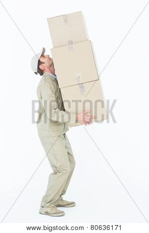 Full length side view of delivery man carrying boxes against white background