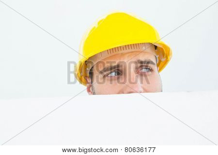 Close-up of repairman wearing hard hat while looking away in front of billboard over white background