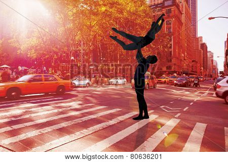 Ballet partners dancing gracefully together against new york street