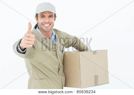 Portrait of happy delivery man gesturing thumbs up while carrying box over white background