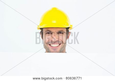 Portrait of happy male architect with bill board over white background
