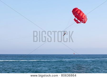 People are flying in a parachute over the sea.
