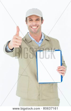 Portrait of happy delivery man gesturing thumbs up while showing blank paper on clipboard over white background