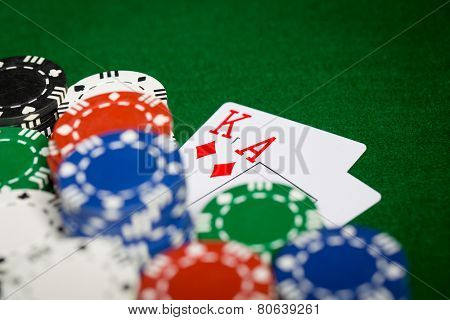 gambling, fortune, game and entertainment concept - close up of casino chips and playing cards on green table surface