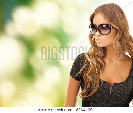 people, fashion, elegance and style concept - beautiful young woman in shades green background