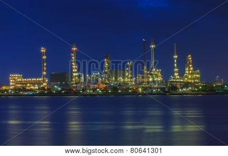 Beautiful Landscape Of Oil Refinery Plant Lighting In Industry Estate Beside River On Blue Dusky Sky