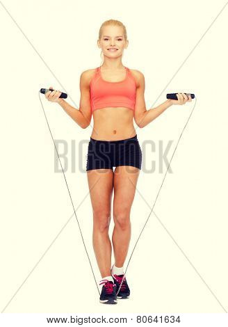sport, excercise and healthcare - smiling sporty woman with skipping rope