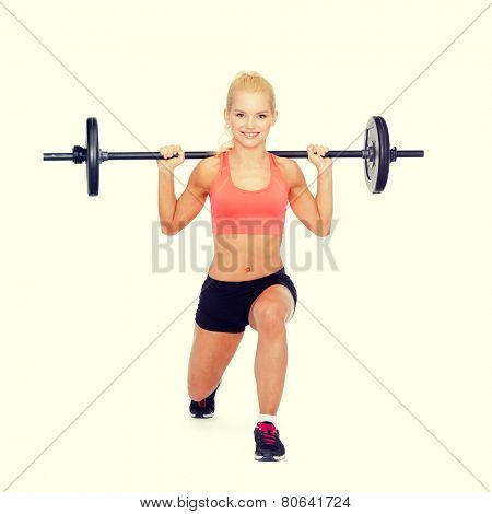 fitness, sport and exercise concept - smiling sporty woman with barbell doing split squat or lunge