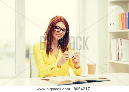 education, entretainment and technology concept - smiling student girl in eyeglasses with smartphone, books and takeaway coffee at school