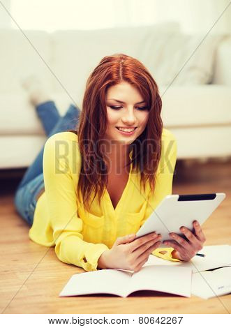 business, education and technology concept - smiling female student with notebooks and tablet pc computer at home