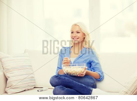 food, happiness and people concept - smiling young girl with popcorn ready to watch movie at home
