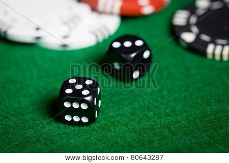 gambling, fortune, game and entertainment concept - close up of black dices on green casino table