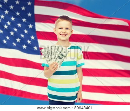 financial, planning, childhood and educational concept - smiling boy holding dollar cash money in his hand over american flag background