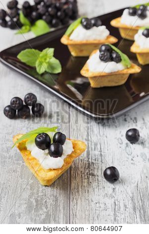 Canape With Cottage Cheese And  Black Berries Of Mountain Ash