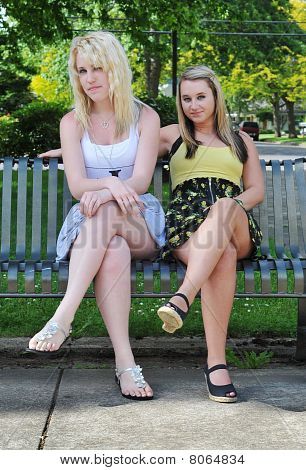 Two Girl Friends Sitting On A Bench