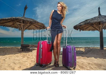 Young female stay with a suitcases on the beach
