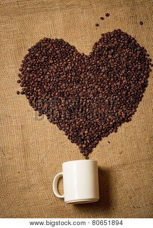 Heart Of Coffee Beans Going From White Mug Lying On Canvas