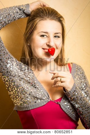 Smiling Woman In Dress Holding Decorative Heart At Lips