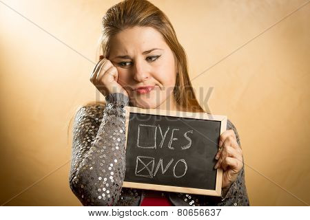 Sad Woman Holding Blackboard With Checked Negative Answer