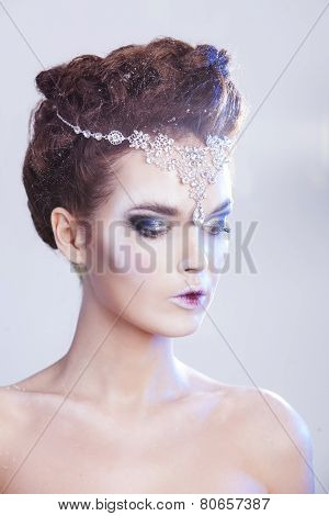 Beauty woman over blue winter background with luxury accessories. Snow queen. Make-up